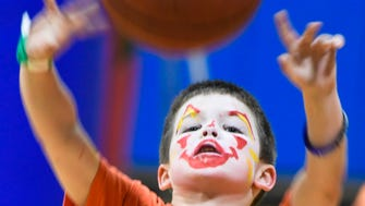 Sporting a freshly painted face, Jordan Barron, six years-old, shoots some hoops at the Henderson YMCA Healthy Kids Day event Saturday, April 29, 2017.