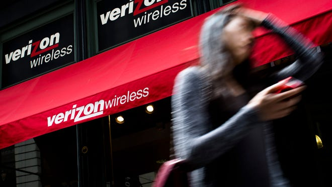 Verizon Wireless and Sprint will pay more than $500,000 to New Jersey and offer consumer refunds to settle accusations that it crammed wireless telephone bills. A pedestrian uses her cellphone as she passes a Verizon Wireless store on Broadway in Lower Manhattan in this 2013 file photo.