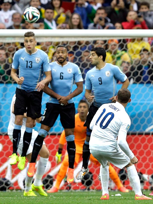 England's Wayne Rooney tries to get the ball over the Uruguay defensive wall on a free kick during the group D World Cup soccer match between Uruguay and England at the Itaquerao Stadium in Sao Paulo, Brazil, Thursday, June 19, 2014.  (AP Photo/Kirsty Wigglesworth)