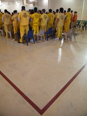 Jail inmates stand during a Catholic Mass celebration