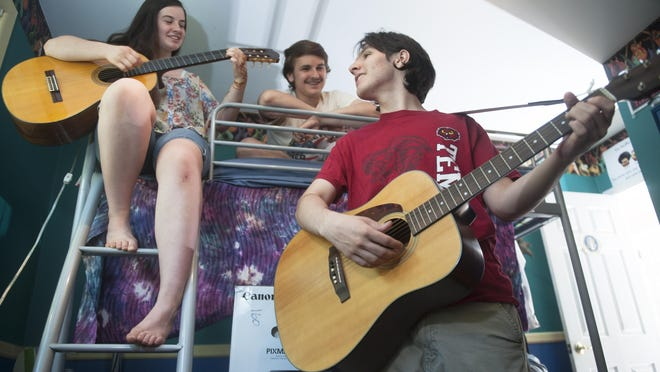 Patrick Oberstaedt, 18 (right), who will study music education at Temple University, plays guitar with his sister Melissa, 14, as their brother Matthew, 16, looks on in their Cherry Hill home.