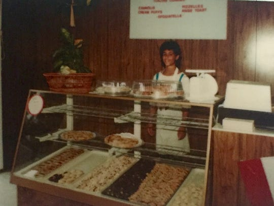 Angela Ranalli-Cicala stands behind a bakery case filled with cookies she helped make at the age of 13 for her family's Maple Shade business.