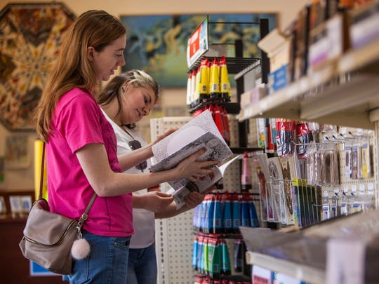 Meghann Eide (left) and Gillian Jones (right) look through adult coloring books Wednesday at Color Country Art Supply in Cedar City.