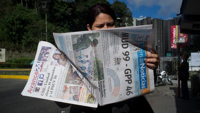 A woman reads a daily newspaper in Caracas, Venezuela, that shows the number of legislators (99) that opposition obtained in the December elections.