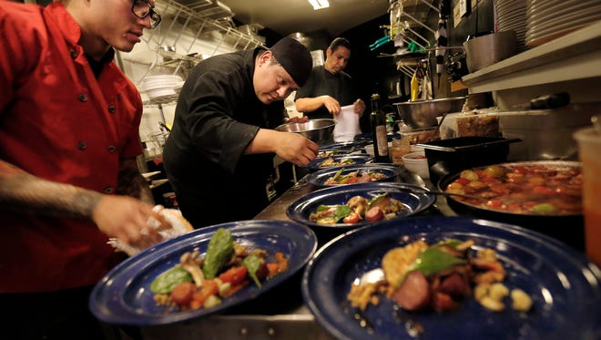 Chef Robert Garay, center, plates the salad course along with sous chef Josh Baray, left, as they prepared a five-course dinner Wednesday night at the Dark Horse Tavern, 115 Durango. The culinary event challenged two chefs, Chef Robert Garay and Chef Lawrence Acosta, to create dishes with the same ingredients but in each of their specialties.