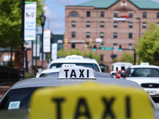 Cabs wait on Rosa Parks Drive at the Wilmington Amtrak station late last month. Taxi drivers say ride-share operators such as Uber are poaching their customers from high-volume locations in Delaware.