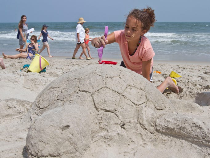 Theresa Kay, 11, of Philadelphia, PA, creates a sea turtle with her family during the contest. Families participate in the Barnegat Light sand scupting contest held at the 25th Street beach. Barnegat Light, NJ Thursday, July 3, 2014 Doug Hood/Staff Photographer