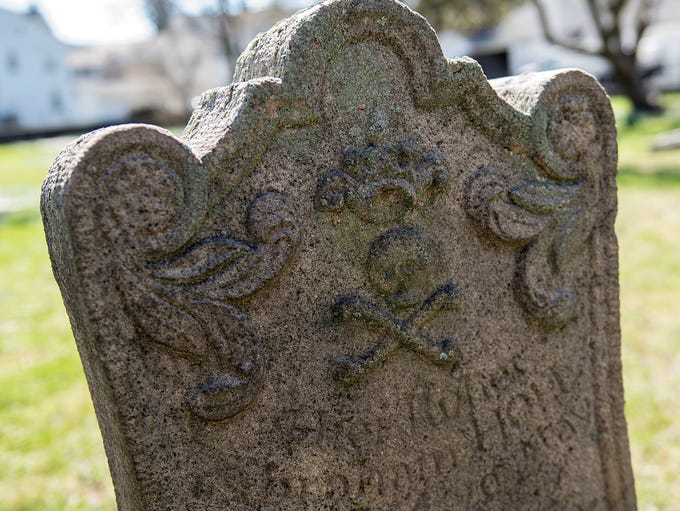 A headstone with a skull and crossbones is one of many