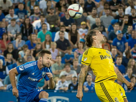 Columbus Crew's Emanuel Pogatetz heads the ball over Montreal Impact's Jack McInerney during the first half of an MLS soccer game in Montreal on Saturday, July 11, 2015. (Peter McCabe/The Canadian Press via AP)