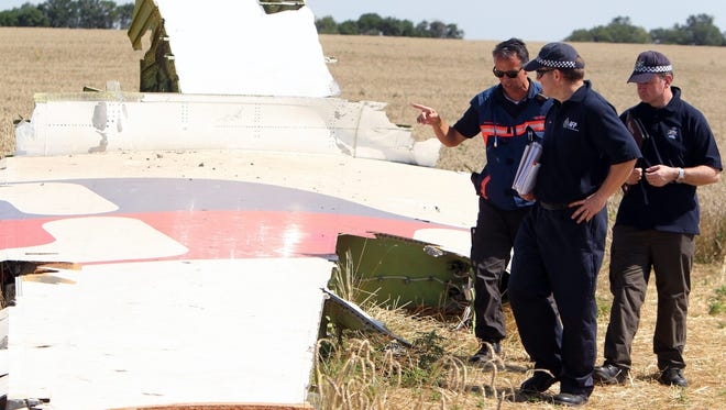 Australian and Dutch investigators examine a piece of debris of Malaysia Airlines Flight MH17 plane, near the village of Hrabove, Ukraine on Aug. 1, 2014.