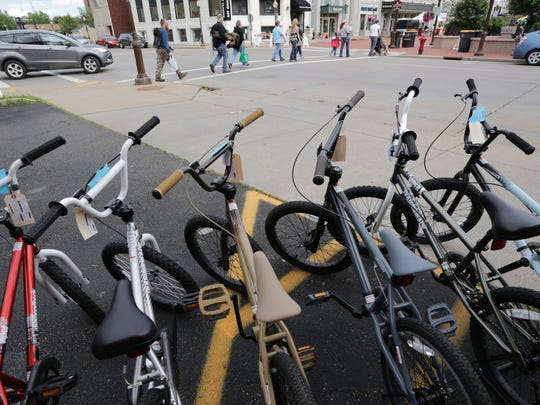 Bikes sit outside while pedestrians headed to the concert on the 400 Block cross Scott Street as Shepherd & Schaller's Sporting Goods gets a jump on the Sidewalk Sales in 2014.