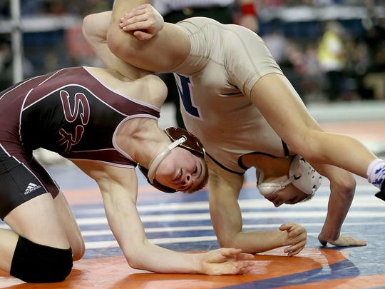 South Kitsap's Xavier Eaglin takes down Mead's Chase Randall during the Mat Classic Championships at the Tacoma Dome on Saturday, Feb. 17, 2018.