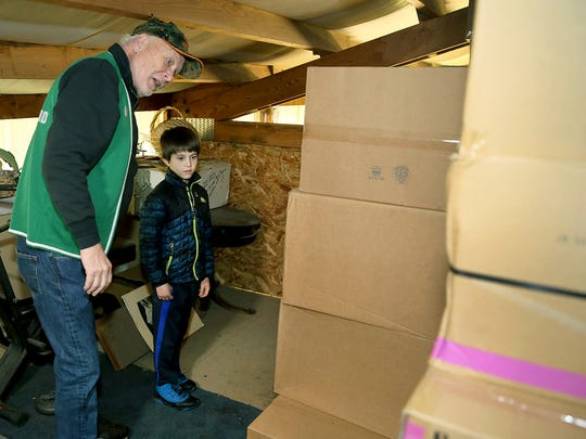 Zachary Darner, 8, and Ron Weekes with some of the boxes of toys donated by the Port Orchard Eagles Club.