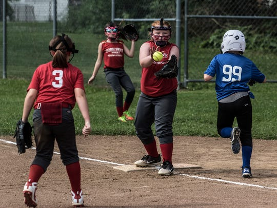 Corsi-Swick Asphalt players complete an out at first base Sunday during a Licking County Shrine Tournament semifinal at Mound City. The Licking Valley 10U entry beat Mound City's Park National Bank to secure a spot in the inaugural softball championship game.