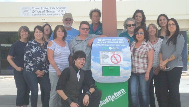 The Youth Substance Abuse Prevention Coalition gathers around the new MedReturn kiosk where Grant County residents can now safely dispose of unused medications at 1106 N. Pope St.  Pictured (from right to left) Back row: Kendra Milligan (Media Contractor, YSAPC), Tom Bate (Fraternal Order, Faith Community), Paul Slatery (Community Member), Christina L. Gutierrez (PIRE Evaluator) and Dianna Perea (First Born Program); Middle Row: Aimee Jaurequi (Silver Schools), Bianca Padilla (JPO), Cindy McClean (Grant County DWI Program), Michael McGee, LADAC, MSW (YSAPC), Mary Alice Murphy (Grant County Beat), Christine Starr (SCPD), Sonya Dixon (Bayard Public Library), Luz Carbajal (SASS), Front kneeling: Cronn Chavez (YSAPC)