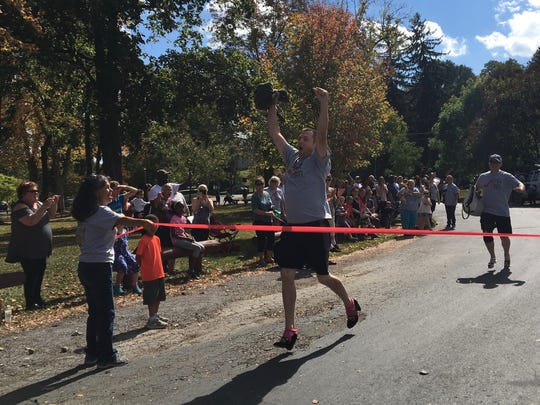 "Andrew McNorton reaches the finish line for the Middle River Regional Jail team to win first place as part of an event to raise awareness for Members of local law enforcement race in high heels at the ""Walk a Mile in her Shoes"" event to raise awareness for domestic and sexual violence, at Gypsy Hill Park in Staunton, Va., on Saturday, Oct. 7, 2017."