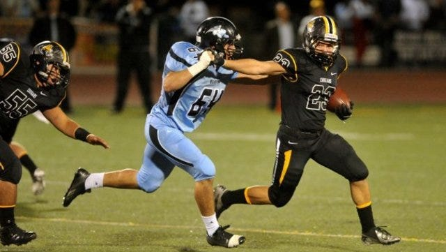 Ventura High School's Tyler Peralta (right) tries to get clear of Buena High School's Joselle Lucas in a Channel League football game at Ventura High on Friday night, November 1, 2013.