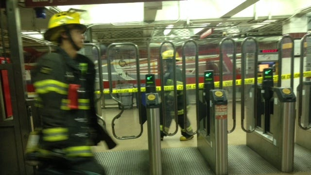 A firefighter goes past the turnstiles at the PATCO station at 8th and Market streets.
