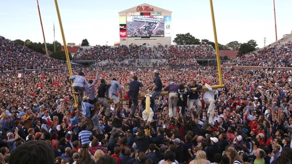 Ole Miss fans work to tear down the goal posts after Saturday's win against Alabama.
