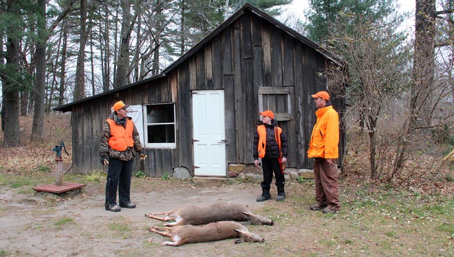 Jim Wipperfurth (left) of Sauk City, talks with Mike Watt (right) and his son Isaac Watt, both of Dodgeville, after a morning of deer hunting on the Leopold Memorial Reserve near Baraboo on the first day of the Wisconsin gun deer season.