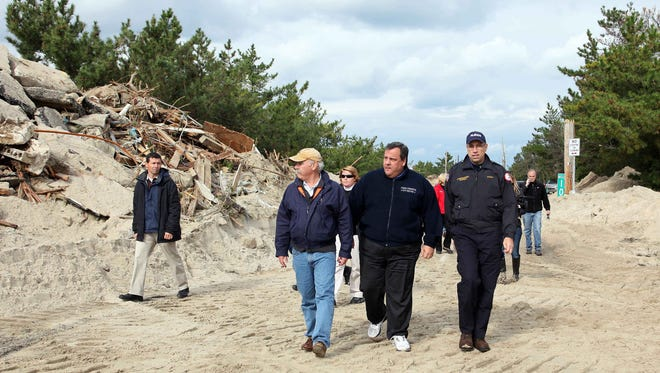 Gov. Chris Christie, center, tours Superstorm Sandy damage in 2012. Christie said Monday that Donald Trump contributed to Sandy relief efforts.