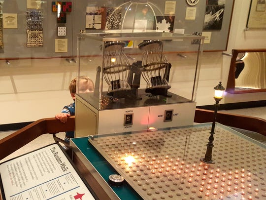 "A young ""Mathematica"" visitor watches the automated dice tumbler of The Random Walk, a machine that demonstrates a kind of anti-probability theory, which states that the past movement or trend of a subject cannot be used to predict its future movement."