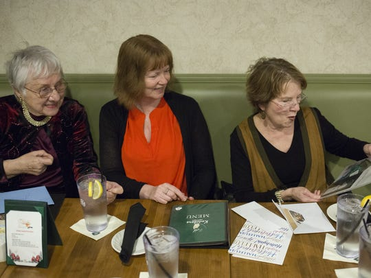 From left, Jean Williams, of Penn Township, Marianne Harbold, of Jackson Township, and Darlene Welter, of York Township, who became friends during jury duty almost twenty years ago, look at photographs of Williams' mother during a gathering. A fourth friend, Nancy Hickman, was unable to attend the dinner.