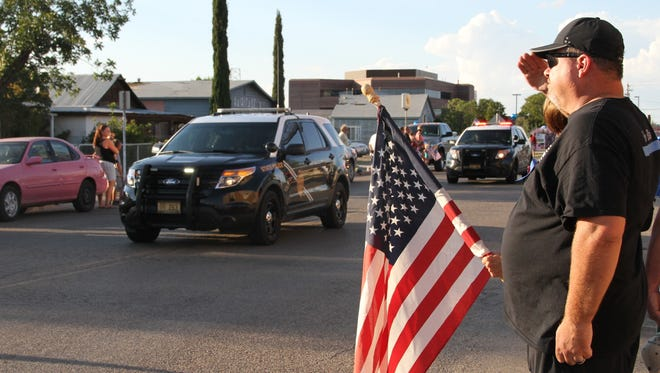 Former Alamogordo Police Department officer Doyle Syling salutes as the motorcade for fallen APD office Clint Corvinus travels by APD headquarters Saturday.
