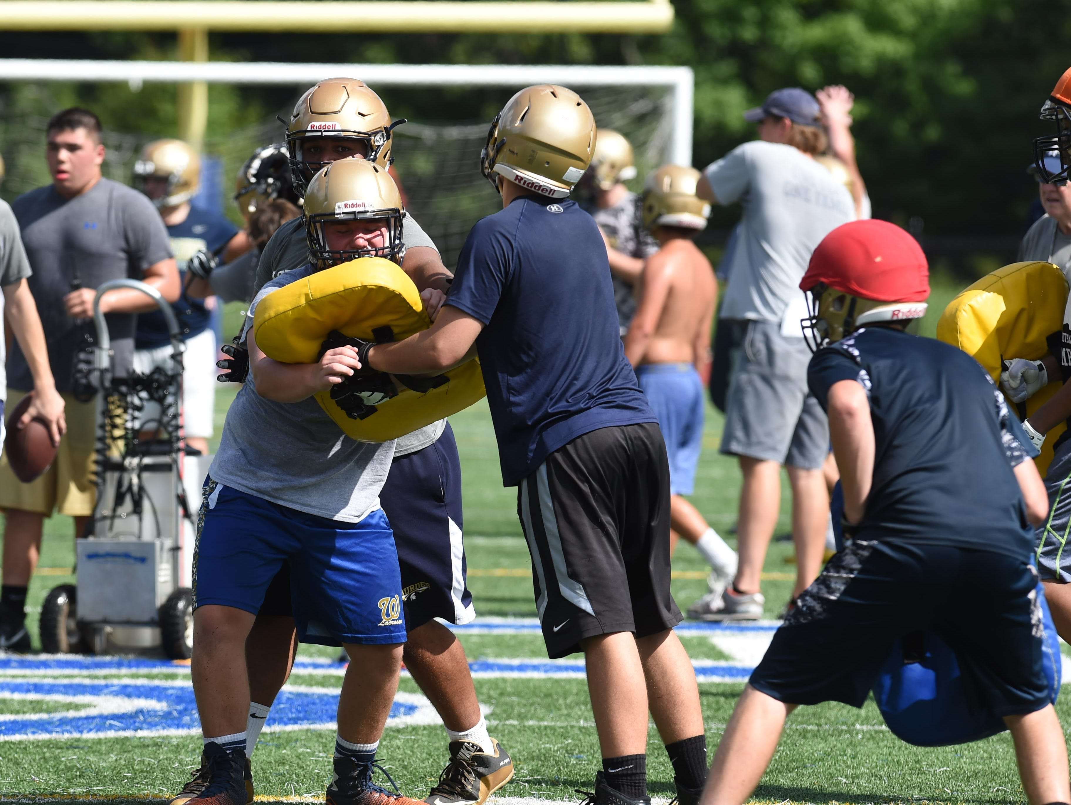 Sophomore Kevin Johansson, left, of Our Lady of Lourdes High School goes for a tackle during preseason football practice.