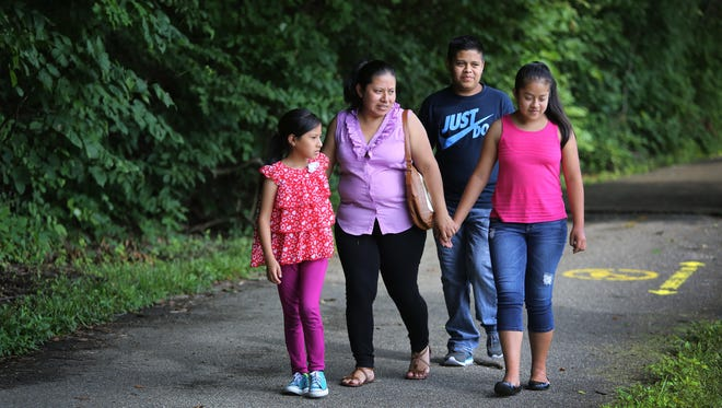 Modesta Escalante and her children, from left, Yury, 8, Yeser, 15, and Marialinda,12, walk through Sharon Woods. The three children have received their Social Security cards, opening the path to citizenship.