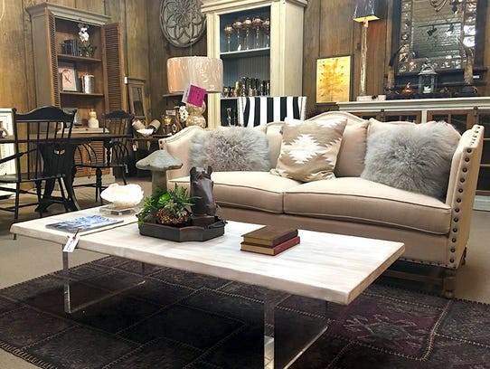 Trendy items, like fur pillows and a lucite table,
