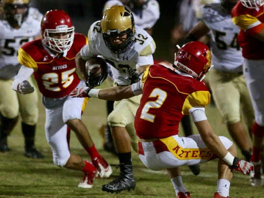 Xavier Prep's Adam Gil carries the football against Palm Desert on Friday night in early high school football action.