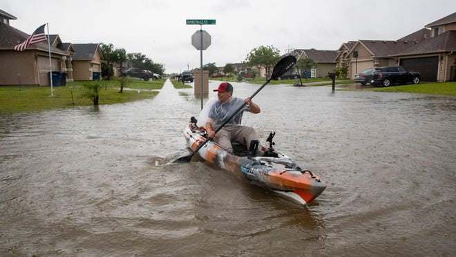 A man kayaks down a flooded street in Corpus Christi on Monday. South Texas has experienced heavy rain as a storm system in the Yucatán Peninsula strengthens. It is now considered a tropical depression, and meteorologists say it could become a tropical storm Tuesday.