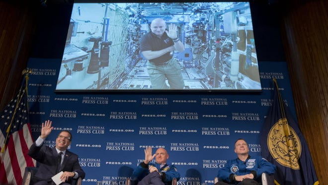 John Hughes, left, of Bloomberg News and president of the National Press Club, is joined on stage by NASA astronauts Mark Kelly, center, and Terry Virts, right, as they talk with Mark's identical twin brother Scott Kelly, who appears via video hookup from the International Space Station on Sept. 14, 2015.