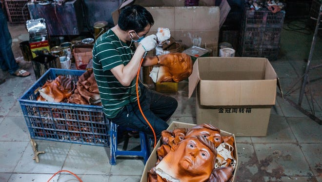 A worker paints a mask of Donald Trump in Shenzhen, China.