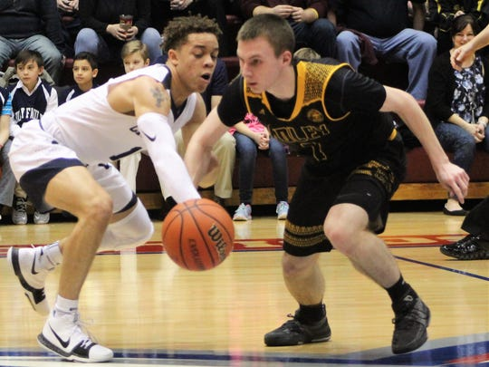 Cranbrook Kingswood junior Torrell Williams (left) slaps the ball away from a Bishop Foley player during Sunday's Catholic League C-D Division title game at Calihan Hall.