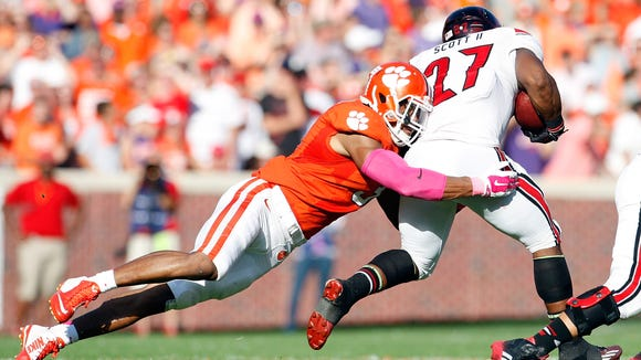 CLEMSON, SC - OCTOBER 11: Vic Beasley #3 of the Clemson Tigers makes a tackle on L.J. Scott #27 of the Louisville Cardinals during the game at Memorial Stadium on October 11, 2014 in Clemson, South Carolina. (Photo by Tyler Smith/Getty Images)