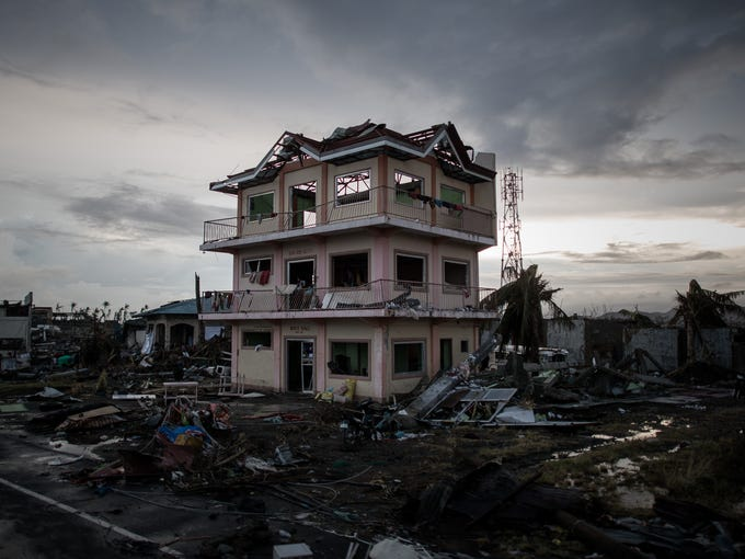 A the sun sets over a house damaged by Typhoon Haiyan outside the airport in Tacloban, on the eastern island of Leyte on November 12, 2013 after Super Typhoon Haiyan swept over the Philippines. The typhoon that destroyed entire towns across the Philippines is believed to have killed more than 10,000 people, which would make it the country's deadliest recorded natural disaster.  TOPSHOTS      AFP PHOTO/Philippe Lopez        (Photo credit should read PHILIPPE LOPEZ/AFP/Getty Images)