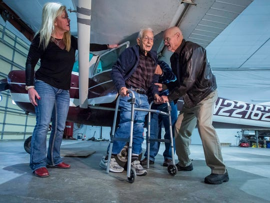 Ernie Smith of Red Oak, Iowa, center, is helped out of at Cessna 150 by his son, Mike Smith, right, and Brenda Nelsonof Atlantic, left, after celebrating his 100th birthday by taxiing because of inclement weather at the Red Oak Airport Thursday, Dec. 21, 2017, surrounded by family and fellow pilots. Ernie is the world's oldest licensed pilot but his medical is lapsed.