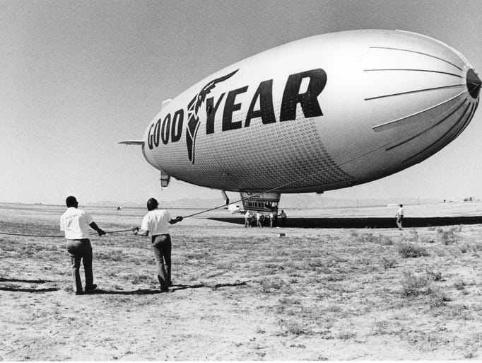 The Goodyear Blimp is guided by men before taking off
