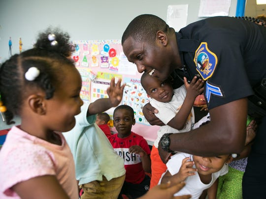 Wilmington Police officer Michael Spencer gets a hug from Ra'Kye Purnell and other children at Our Future Christian Childcare Center after reading to the group of kids.
