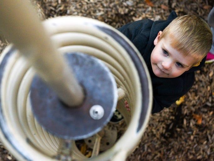 Max Dorhut, 3, climbs on the playground at McKenna