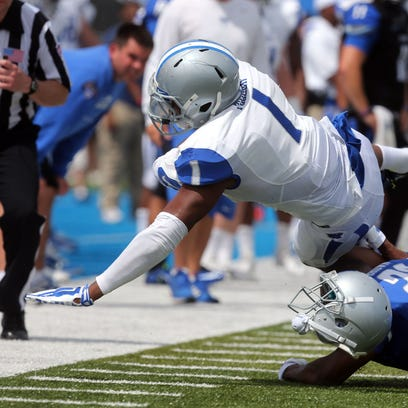 MTSU's Chris Brown loses his helmet as he hits running back Shane Tucker during the Blue-White spring game Saturday.