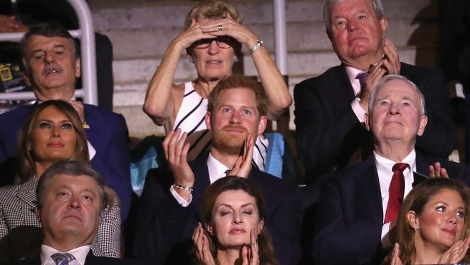 The lady seated behind Harry looks like she's scanning to see where Meghan Markle is.
