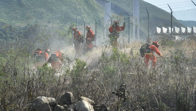 In this file photo, an inmate hand crew creates a containment area around a brush fire along the Santa Clara River near the 300 block of West Santa Maria Street in Santa Paula.