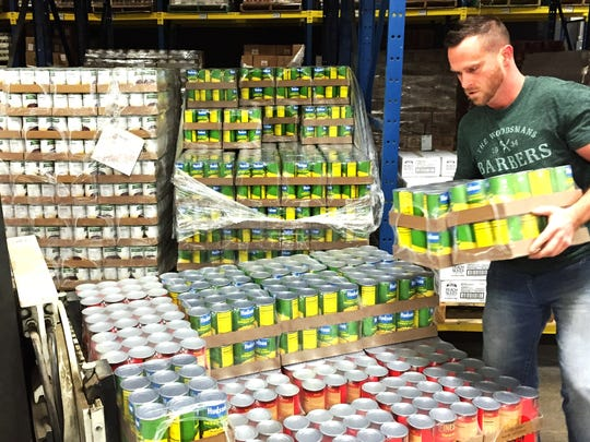 Food Bank of the Southern Tier employee Jeff Ames stacks cans of donated food onto a forklift in December at the food bank's Elmira Heights warehouse.