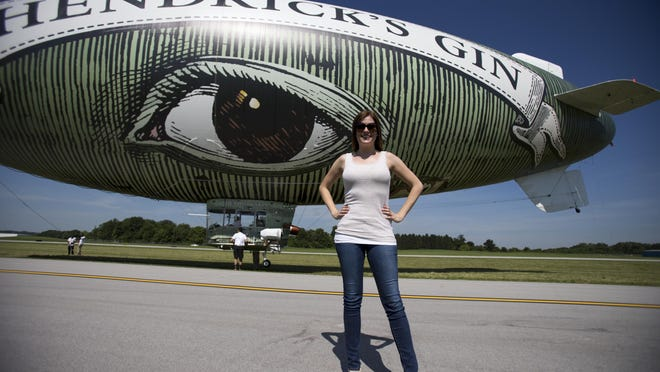 Leslie Bailey poses after riding the cucumber-like Hendrick's Gin blimp, which is flying in the region as part of festivities leading up to Sunday's Crown Royal 400 at the Brickyard, Friday, July 24, 2015.