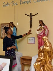"Sister Thea Bowman Catholic School Principal Shae Goodman-Robinson touches Sister Thea Bowman's crucifix on the wall of the school in Jackson on Wednesday. ""(Sister Thea) is probably why I am back here after retiring from Jackson Public Schools,"" Robinson said of the late nun for whom the school is named."