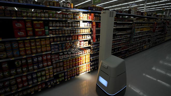 """FILE - In this Nov. 9, 2018, file photo, a Bossa Nova robot scans shelves to help provide associates with real-time inventory data at a Walmart Supercenter in Houston. Robots aren't replacing everyone, but a quarter of U.S. jobs will be severely disrupted as artificial intelligence accelerates the automation of today's work, according to a new Brookings Institution report. The report published Thursday, Jan. 24, 2019, says roughly 36 million Americans hold jobs with """"high exposure"""" to automation, meaning about 70 percent of their work tasks could soon be performed by machines using current technology. (AP Photo/David J. Phillip, File)"""