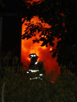 A Kewanee firefighter works to keep a garage fire on Stokes Street Friday from extending to a nearby house.